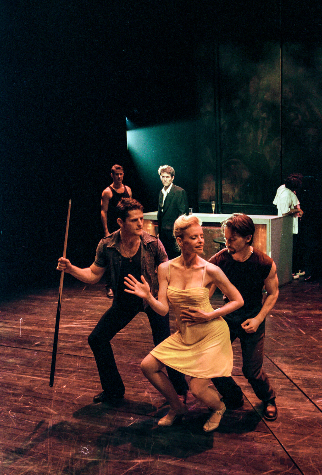 Girl in the Yellow Dress (Deborah Yates) captures the attention of club-goers, Joe (Robert Wersinger) and Johnny (Sean Martin Hingston), as they dance closely behind her.