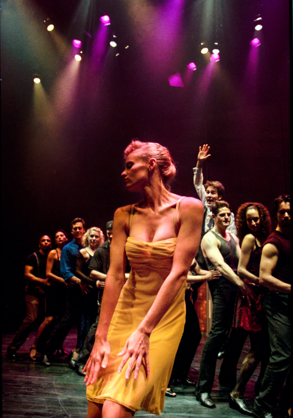 Girl in the Yellow Dress (Deborah Yates) dances downstage center as the club-goers are in a single file line behind her. Boyd Gaines is trying to get her attention as he is behind the line of ensemble members.