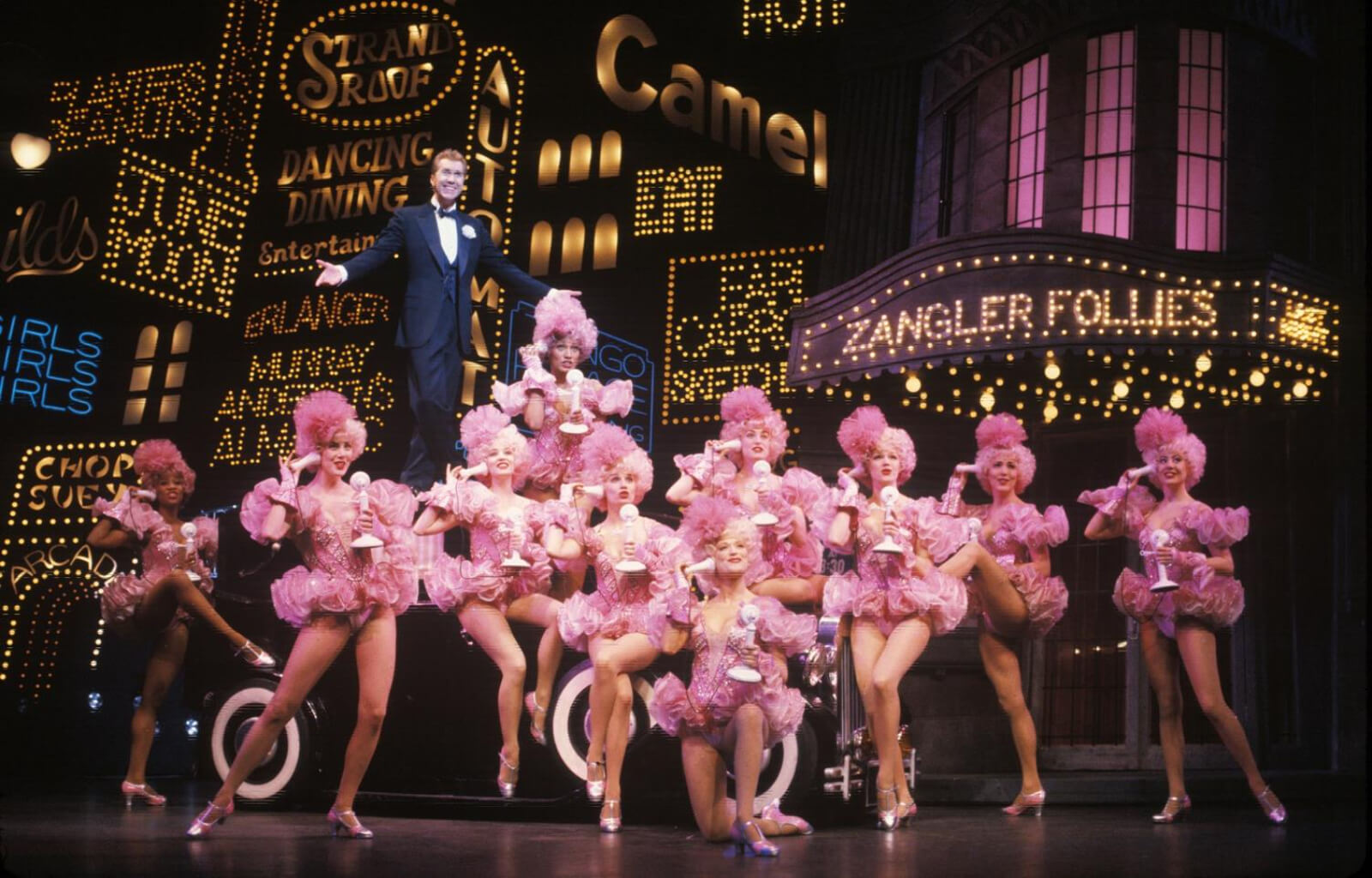 Bobby Child (Harry Groener) stands on top of a car with 10 female dancers all in matching pink tutus posed around him