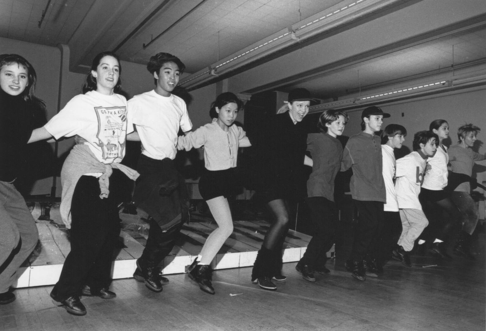 A black and white photo of the cast rehearsing a dance number in a line in a rehearsal studio with Susan Stroman.