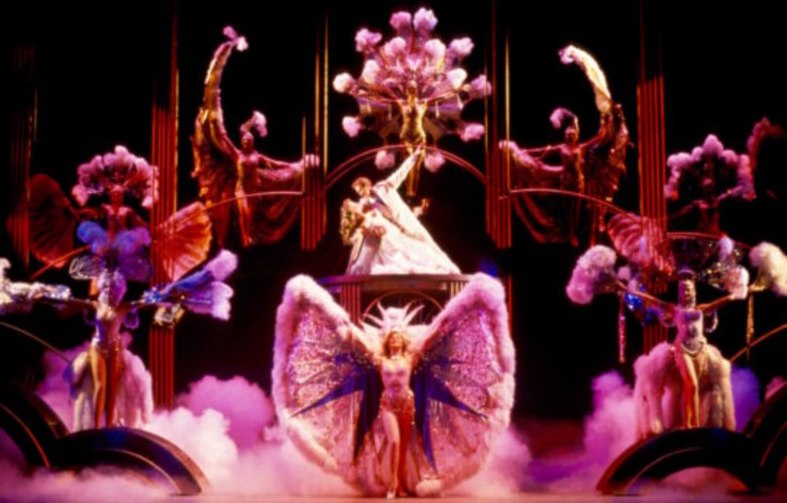 Bobby Child (Harry Groener) gazes at and dips Polly Baker (Jodi Benson) on a platform while surrounded by dancers in elaborate costumes for the Finale
