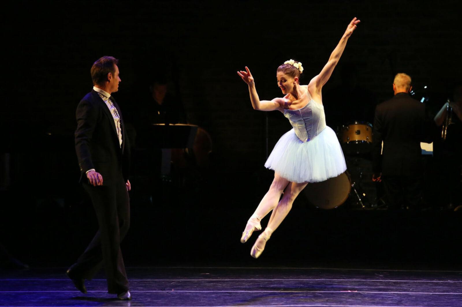 A female dancer in a blue tutu leaps toward her dance partner in a suit.