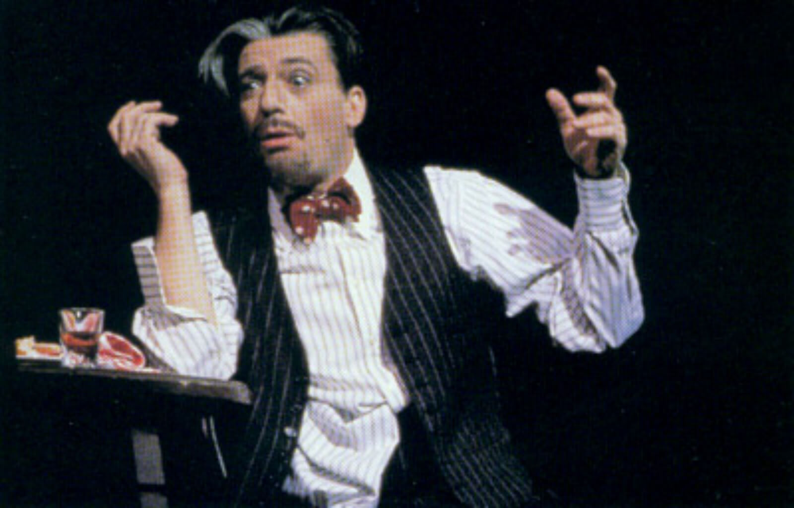 """Bela Zangler (Bruce Adler) sits at a table drunk and dejected for the musical number """"What Causes That?"""""""