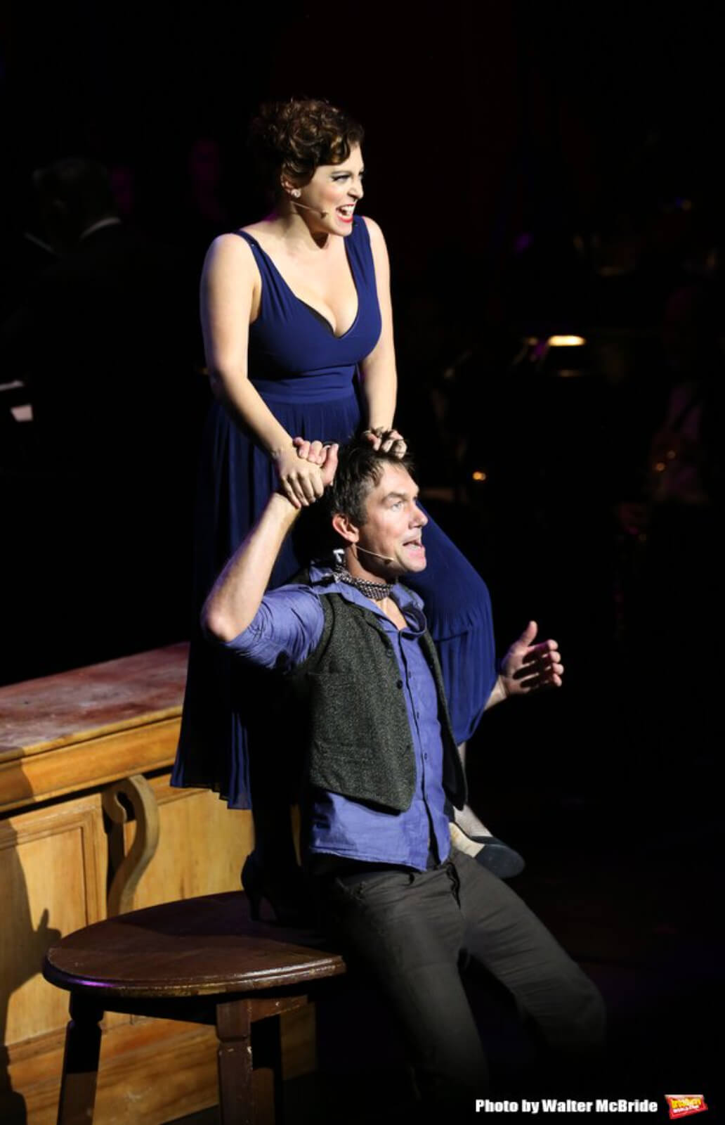 """Irene Roth (Rachel Bloom) standing on a table and pulling the hair of Lance Hawkins (Jerry O'Connell) while performing """"Naughty Baby"""""""