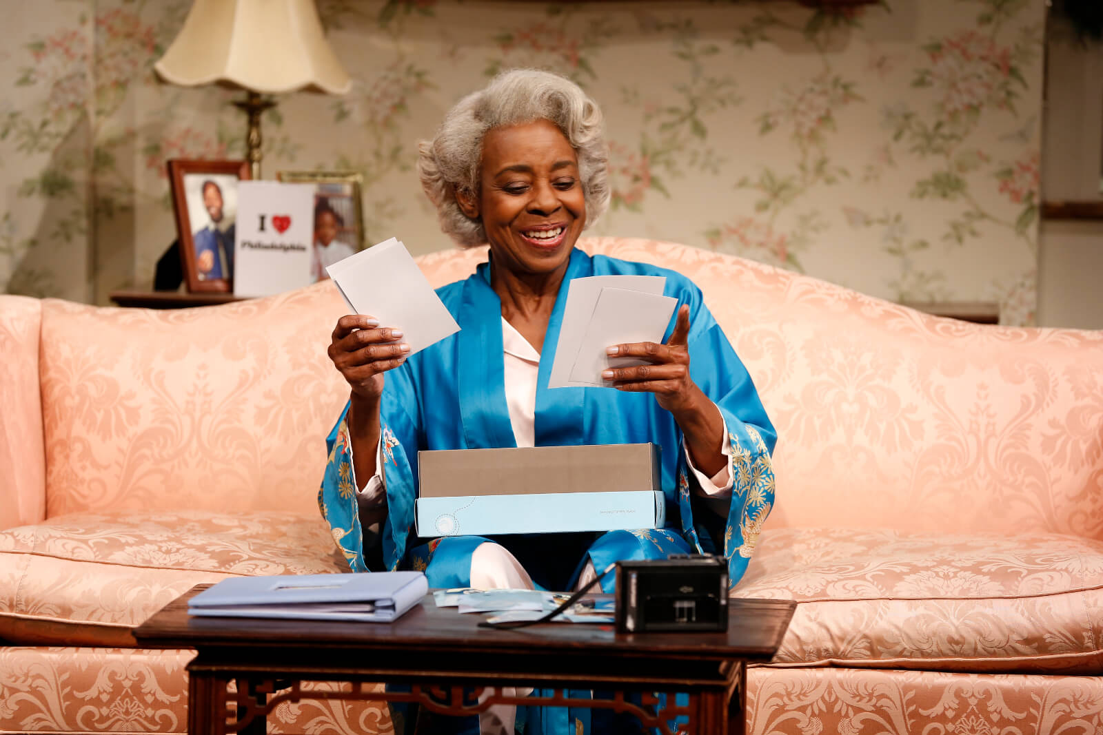 Dotty (Marjorie Johnson) pulls photos out of a shoebox and smiles while sitting on a couch.