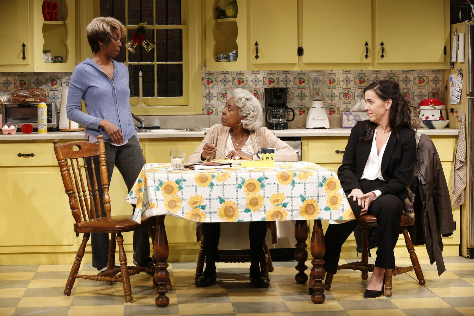 Shelly (Sharon Washington) stands in the kitchen while talking to Dotty (Marjorie Johnson) and Jackie (Finnerty Steeves) at the table
