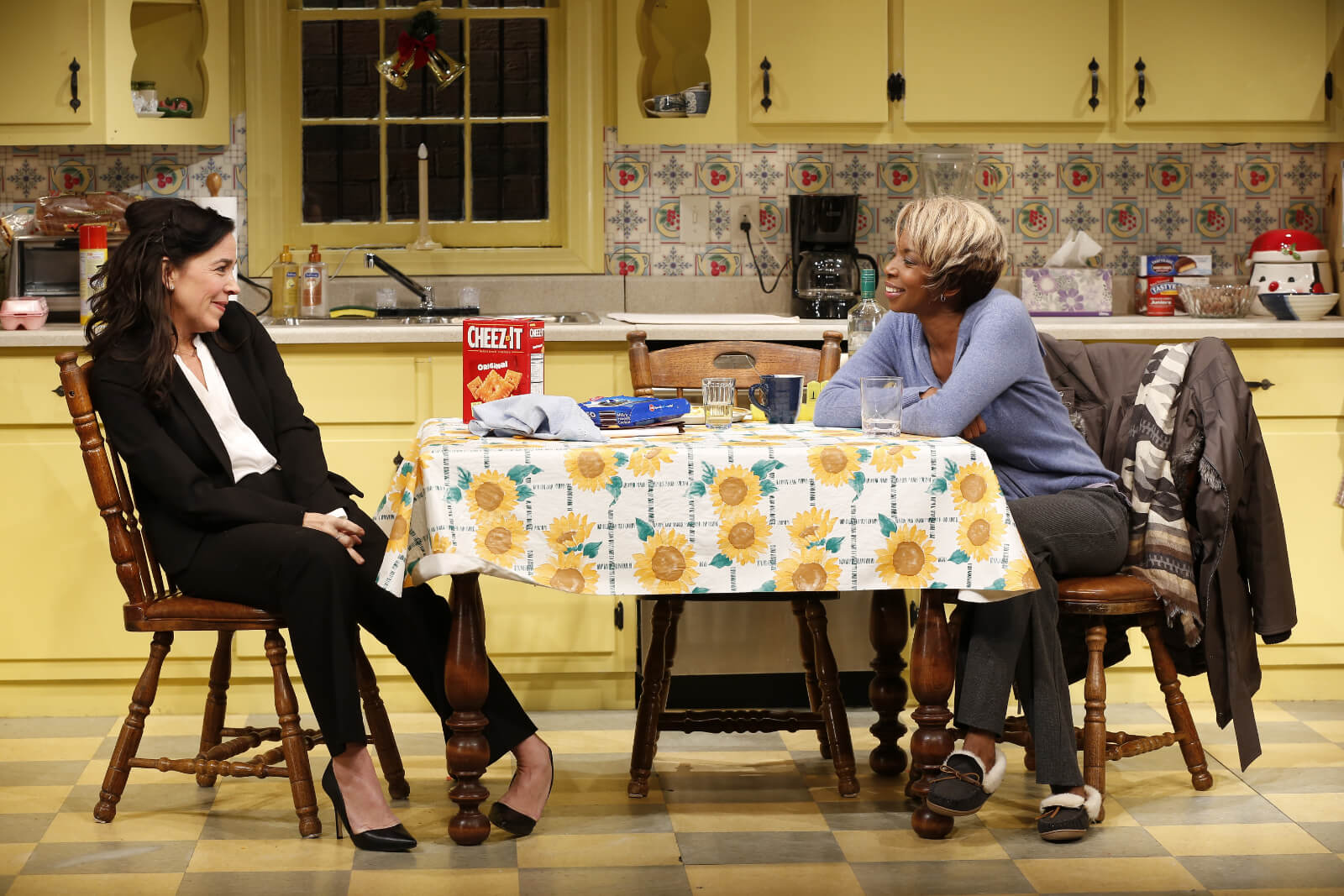 Jackie (Finnerty Steeves) and Shelly (Sharon Washington) smile at each other from the kitchen Table in Dot