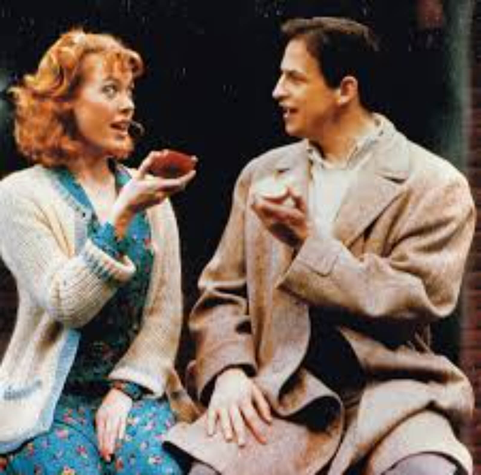 """Flora (Veanna Cox) and Harry (Peter Frechette) sit together for the musical number """"It's Not Every Day of the Week"""" while holding an apple."""