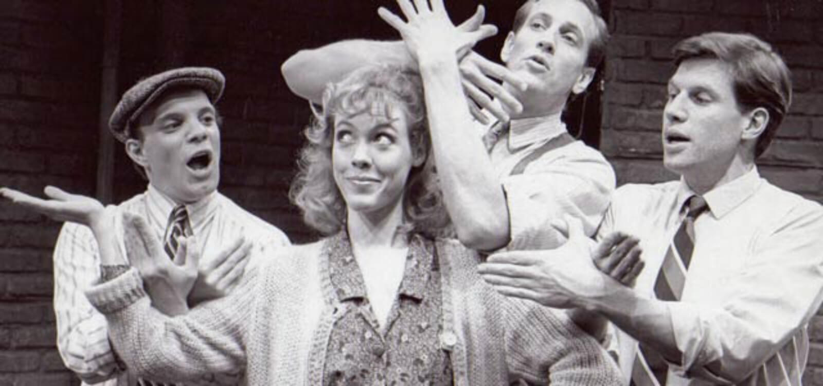 Flora (Veanne Cox) stands in the center with the boys gesturing around her in SONG