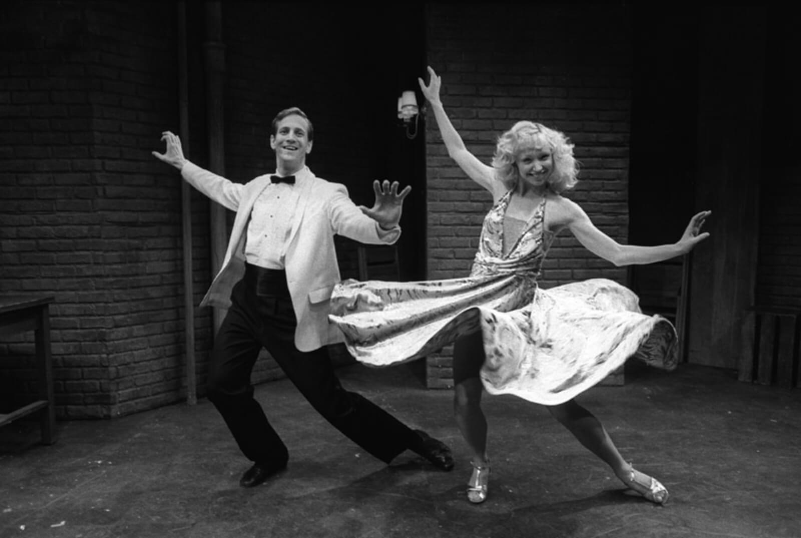 """Maggie (Maggy Gorrill) and Kenny (Dirk Lumbard) lean into a pose with their arms out to their side in the dance number of """"Keeping it Hot"""" from Flora the Red Menace."""
