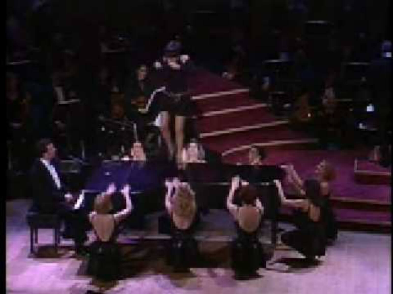 """Liza Minnelli, in a beautiful black dress on top of a grand piano, sings and dances for the audience. She is with the female ensemble performing """"Back in Business""""."""