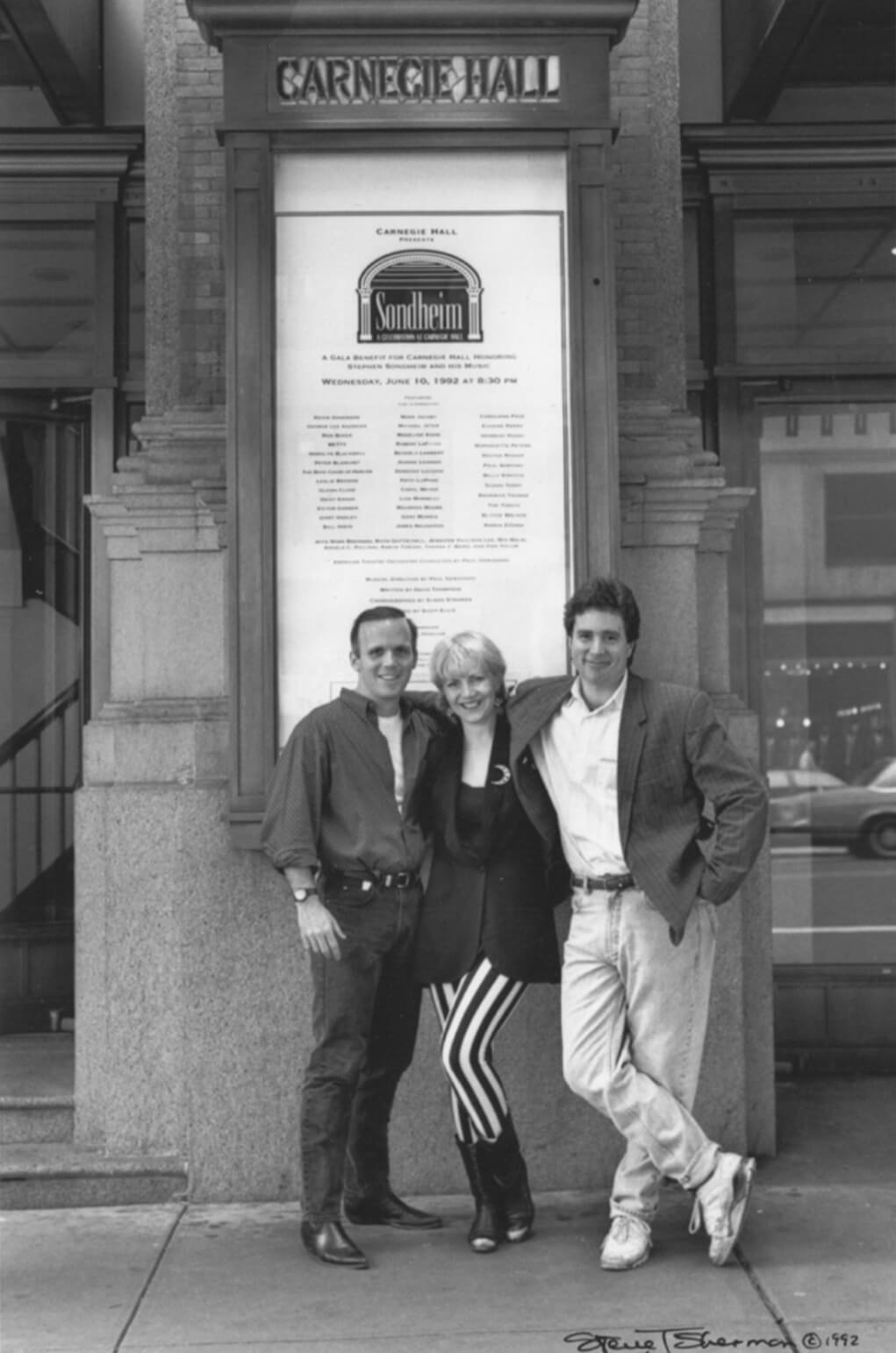 Scott Ellis, Susan Stroman and David Thompson. A black and white photo of the team posing in front of the Sondheim poster at the Carnegie Hall.