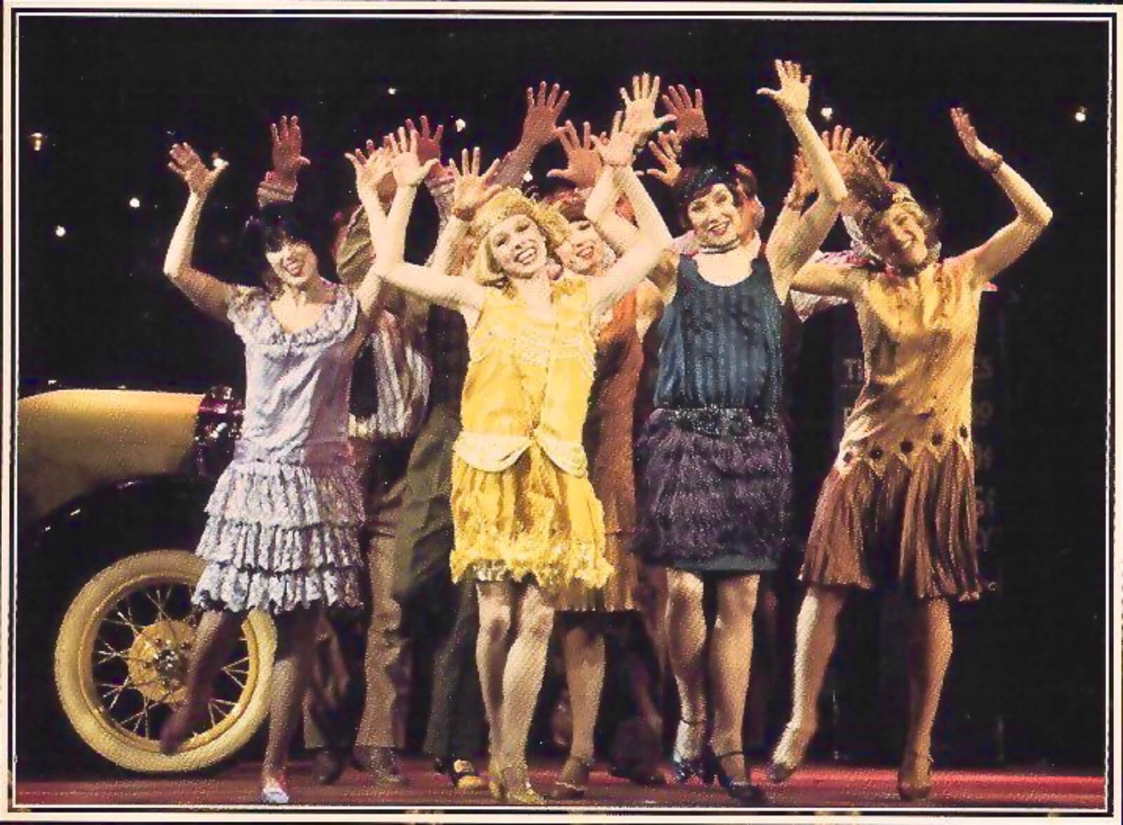 Kim (Tammy Amerson)and the beautiful ladies dancing the Charleston dancing in their elegant outfits, with arms up in the air, waving happily.