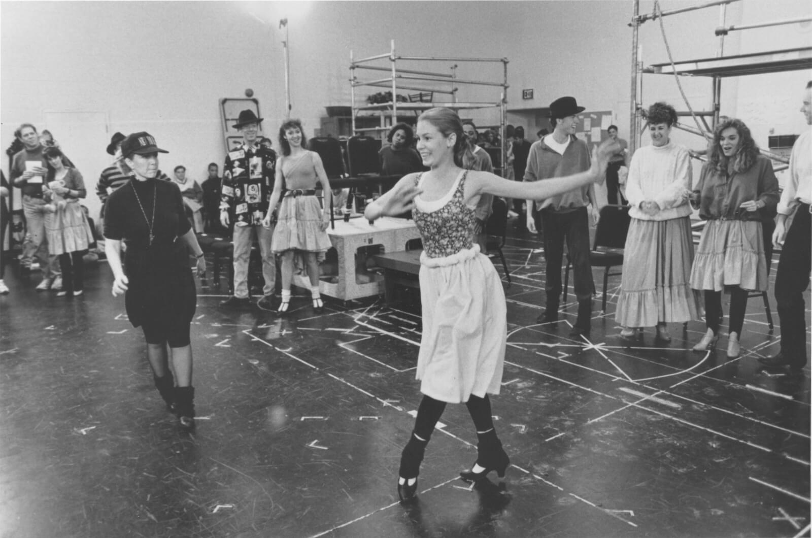 A black and white photo of Susan Stroman rehearsing for Show Boat with Kim (Tammy Amerson). Other ARTISTS watch her in the background.