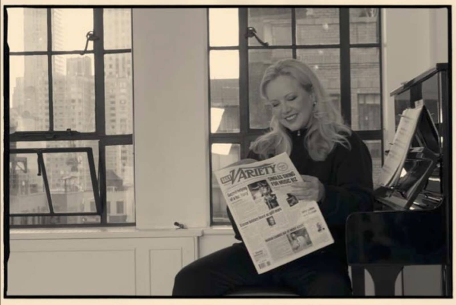Portrait of Susan Stroman in her studio, sitting on the bench next to her piano, reading Variety.