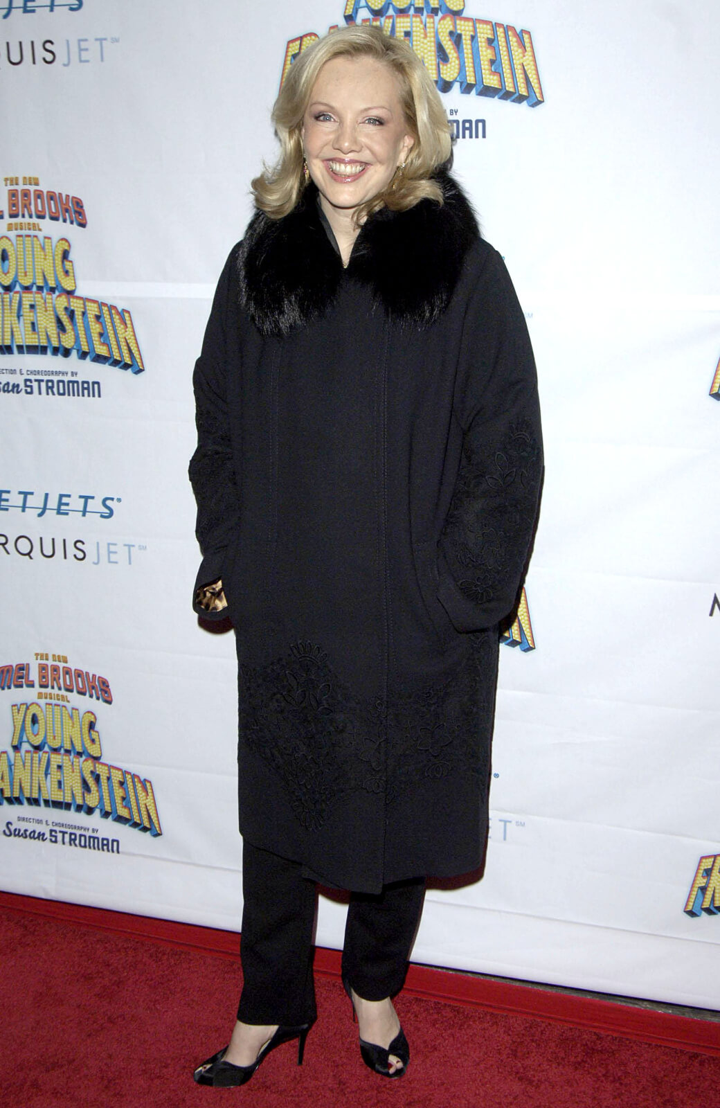 Susan Stroman on the red carpet at the opening night of Young Frankenstein, wearing black heels, pants, and jacket.