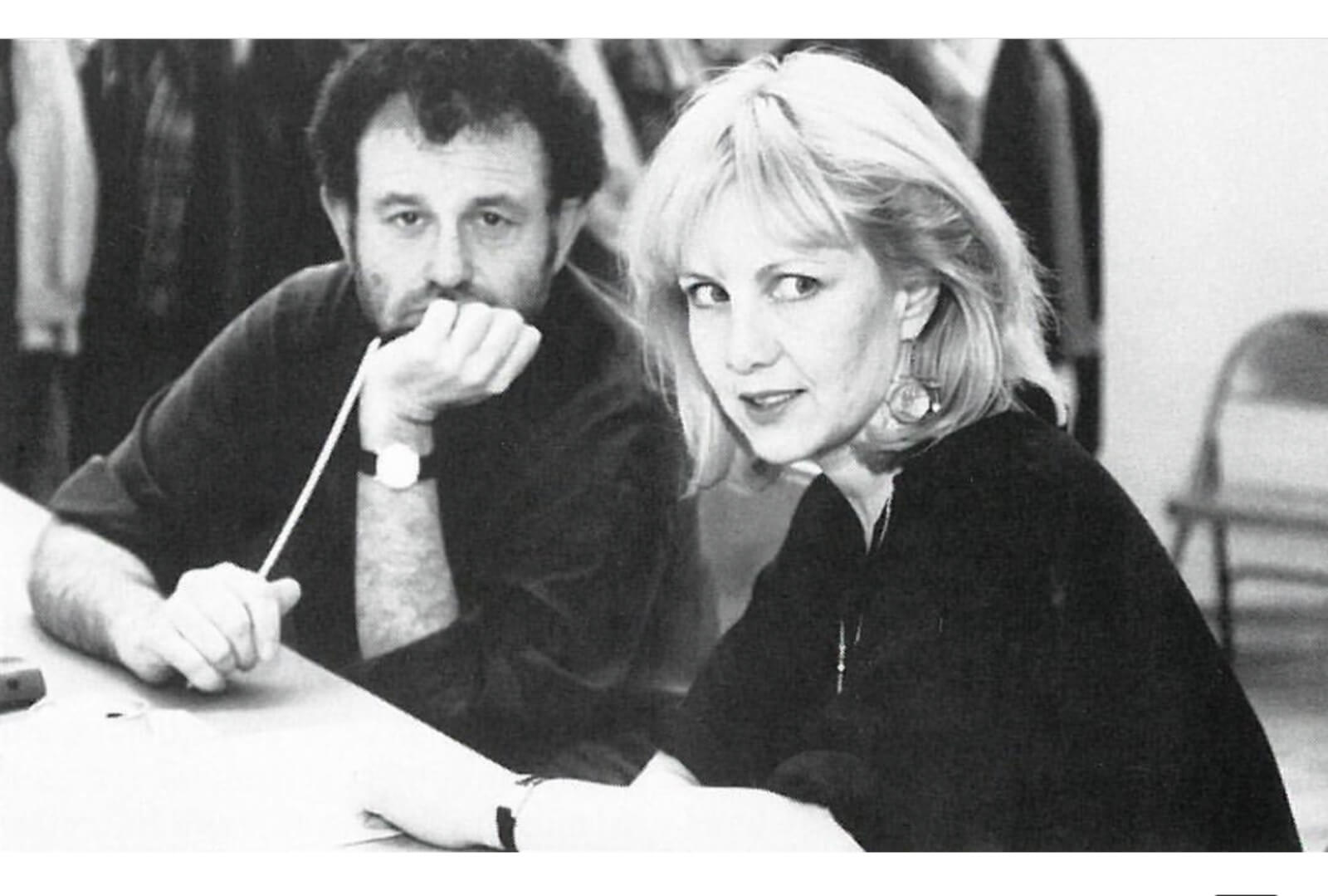 Mike Ockrent and Susan Stroman in rehearsal. Mike is holding a baton and looking at the camera while Stro is looking to the left at something happening in the room.