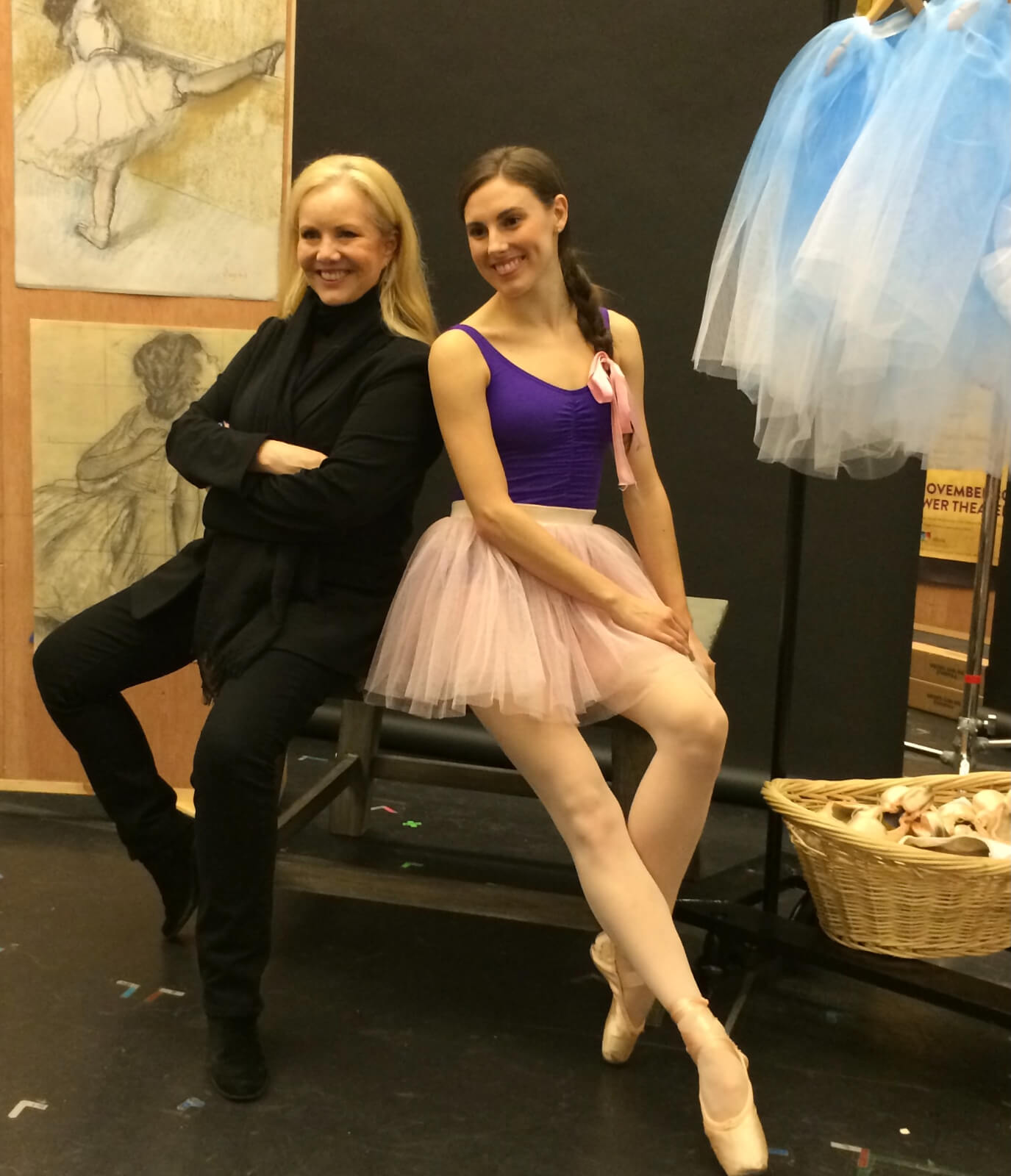 Stro and Tiler Peck, both seated and posing for Little Dancer press photos. Tiler is in a tutu while Stro is in her signature blacks.