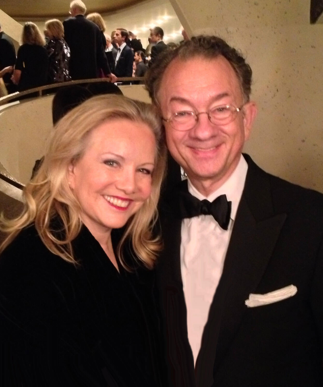 Susan Stroman with long-time collaborator, William Ivey Long. Both are in black tie and audience members can be seen in the background entering or exiting a performance.
