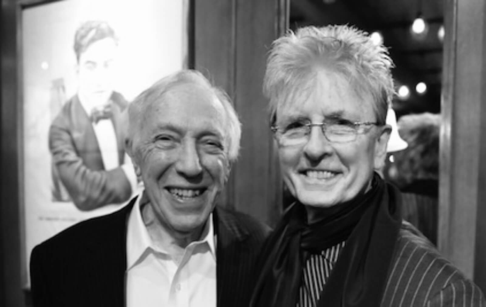 Black and white photo of Bernie Gersten (producer) wearing a black blazer and Paul Huntley (wig designer) wearing a scarf and button up shirt.