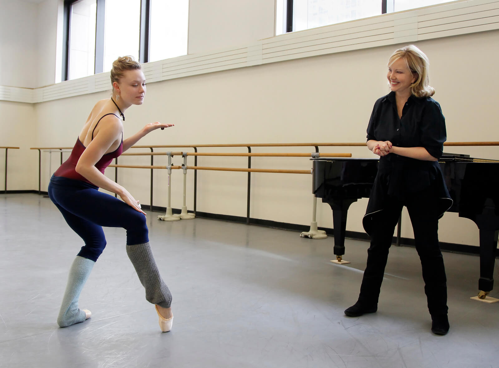 Sara Mearns, slightly kneeling with one pointed foot, in a rehearsal studio with Susan Stroman, standing with clasped hands by a piano.