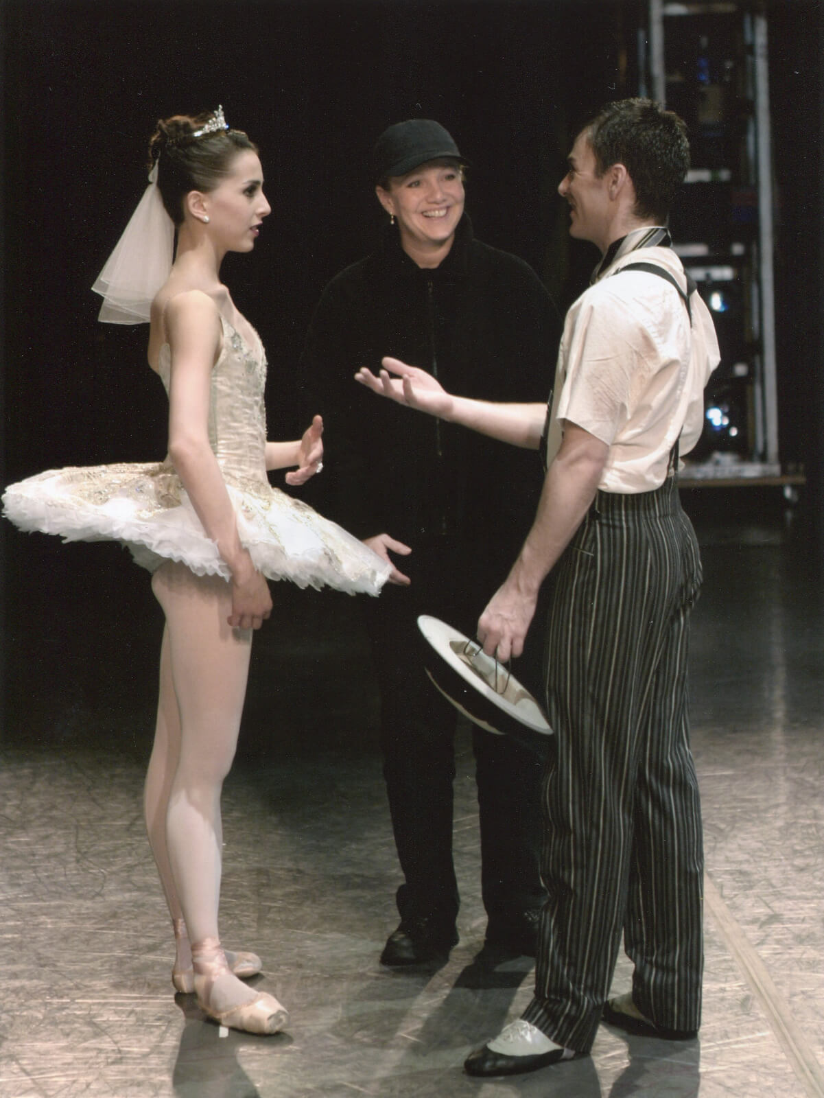 """Stroman (smiling and wearing all black) in between Alexandra Ansanelli (wearing a white tutu) and Tom Gold (wearing pants with suspenders) rehearsing """"Making Whoopee"""" on stage."""