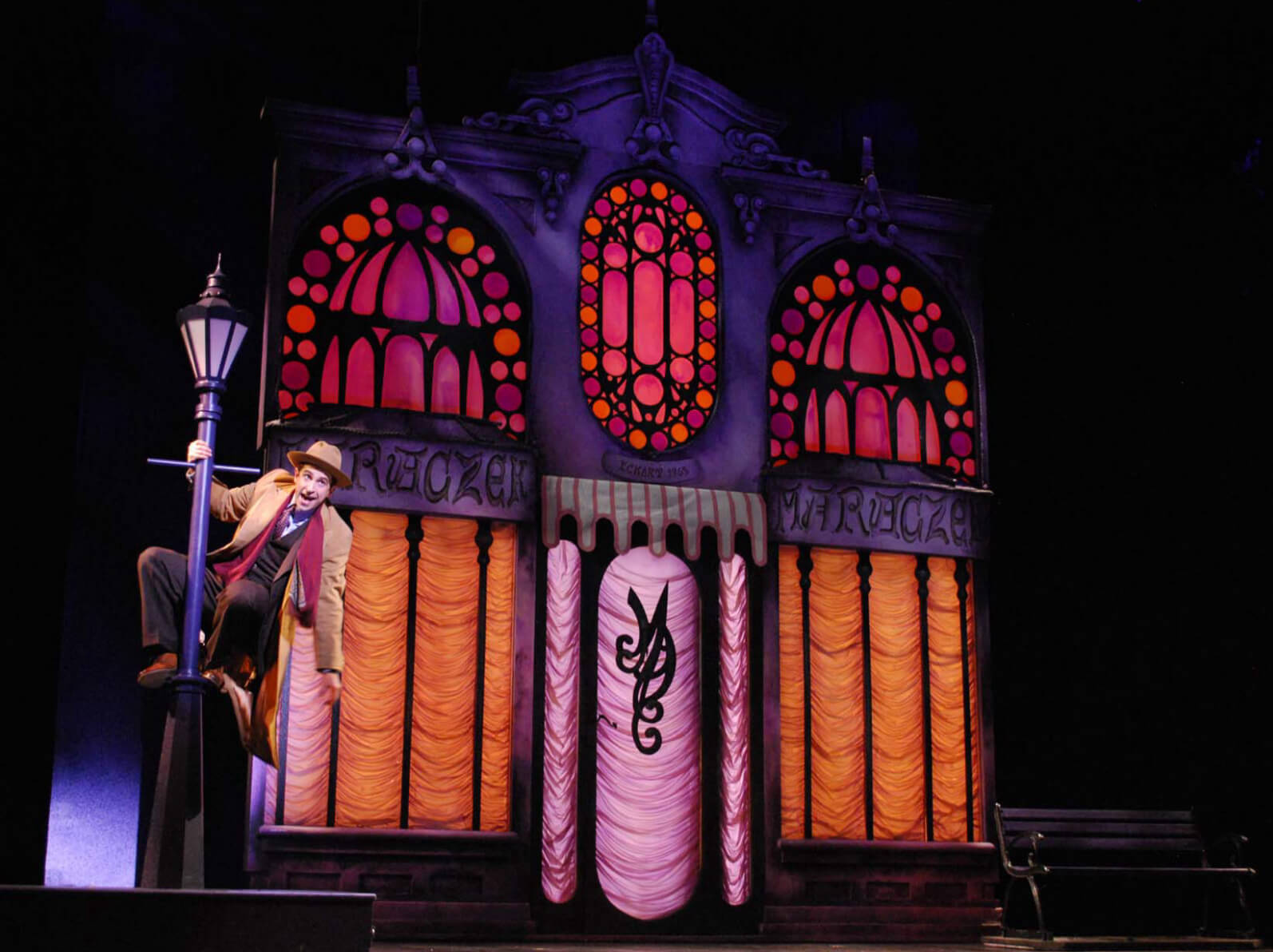 """Brandon Uranowitz singing """"She Loves Me"""". The actor dances on a lamp post in front of a colorful parfumerie in Prince of Broadway."""