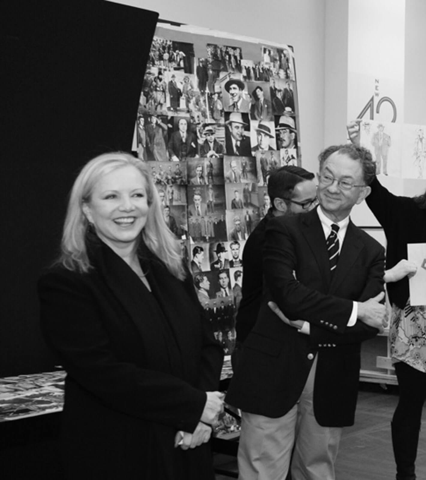 Black and white photo of Susan Stroman and costume designer William Ivey Long at a presentation for Bullets Over Broadway. Research and renderings can be seen on presentation boards.