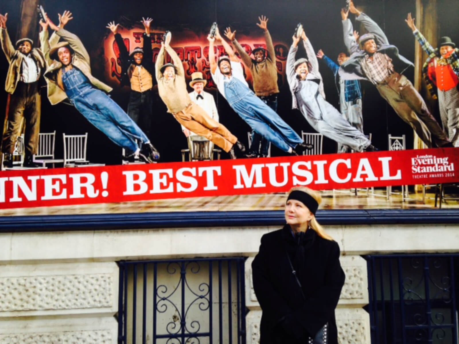 """Susan Stroman (in black jacket and headband) outside of The Scottsboro Boys marquee in London. Show photo and """"Best Music"""" can be seen."""