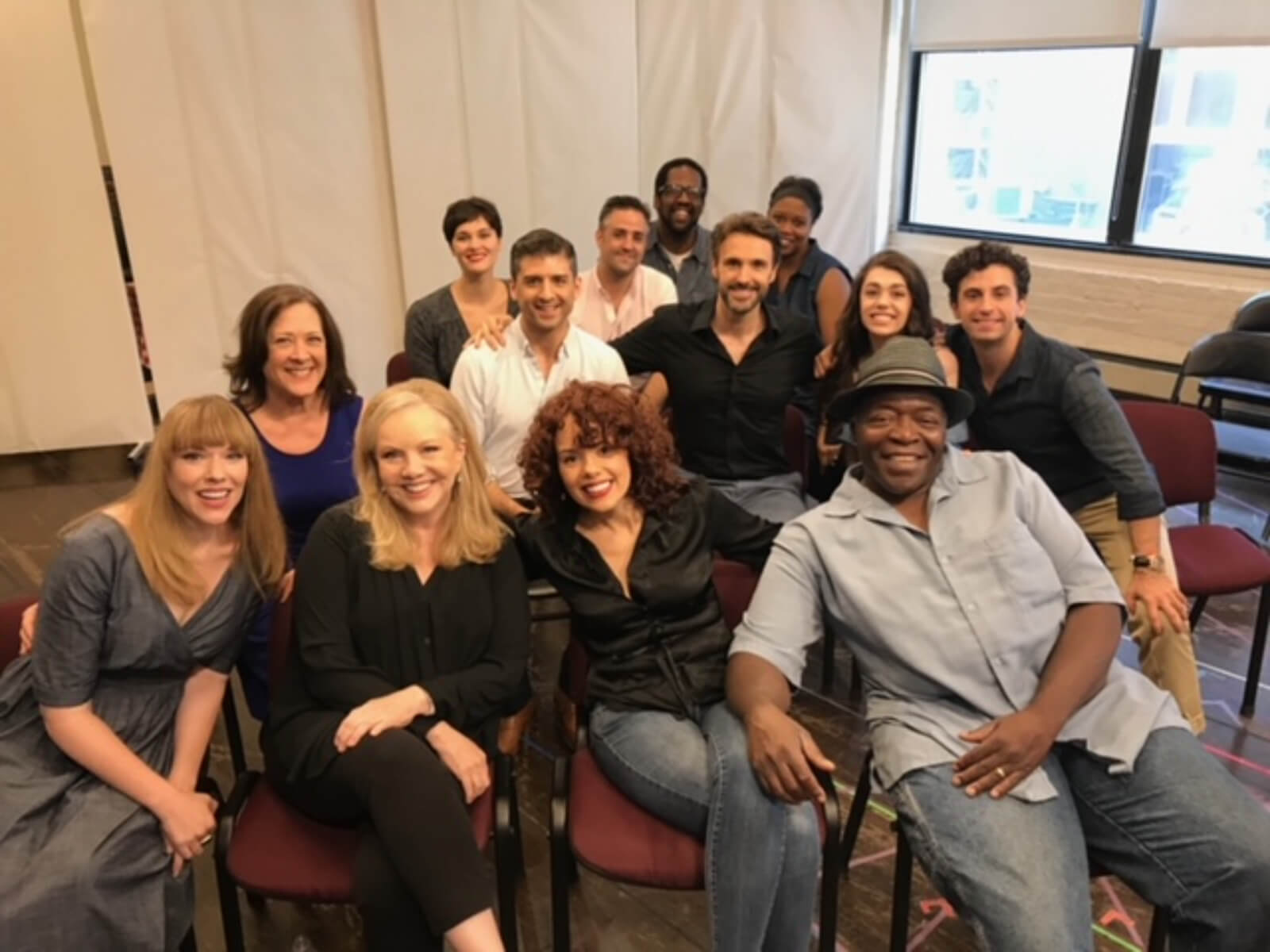 Susan Stroman with the Broadway company of Prince of Broadway. They are in rehearsal sitting in chairs surrounding Susan Stroman.