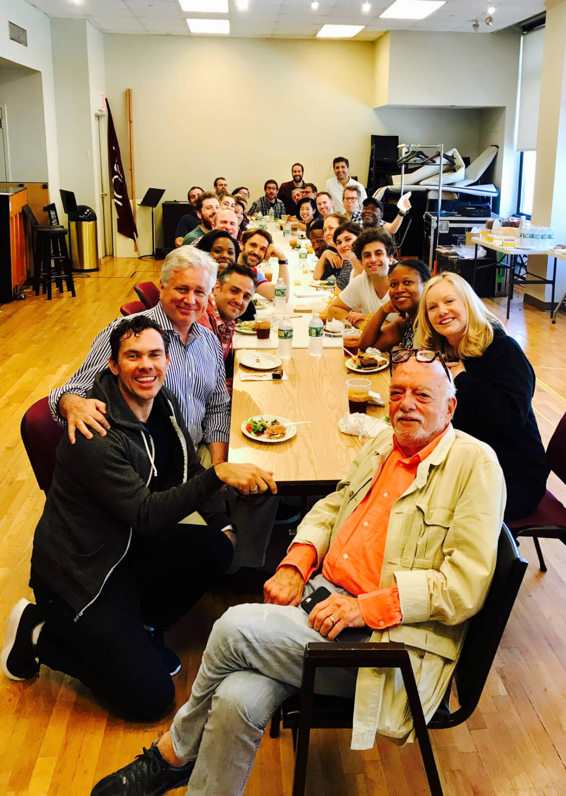 Hal Prince and Susan Stroman having lunch with the Broadway cast and creatives of Prince of Broadway. They are sitting at a long table in a rehearsal studio enjoying their lunch.