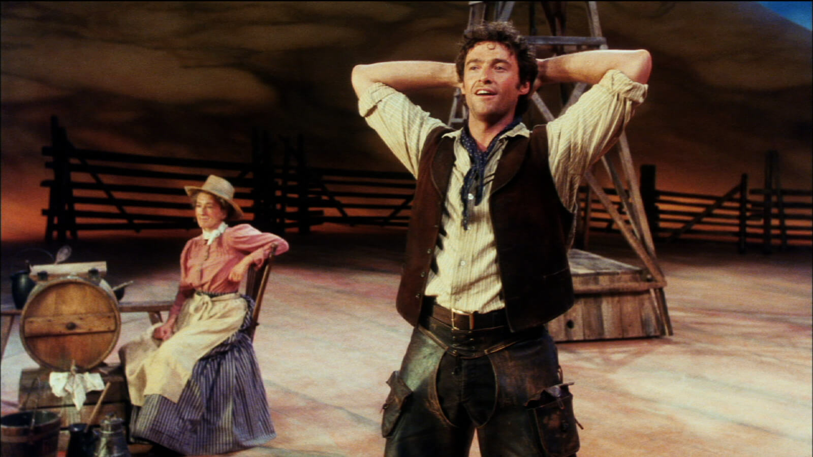 Hugh Jackman in a cowboy outfit, doing a stretch, in the middle of the desert. A woman with apron and hat is sitting behind him, watching over the barrels.