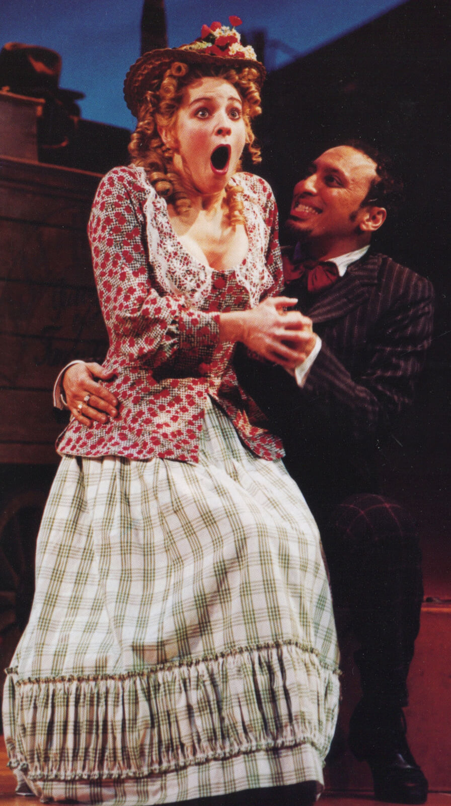 Curly brunette Ado Annie Carnes (Vicki Simon) in a big patterned-dress and hat with flowers gasps as Ali Hakim in a striped tuxedo assists her.