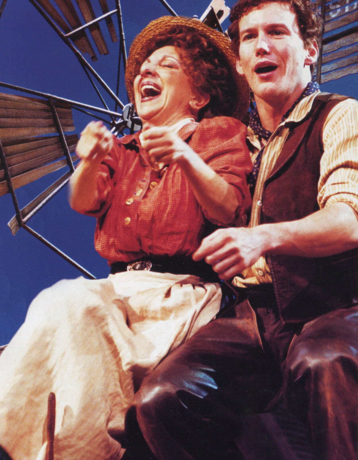 Brunette Aunt Eller (Andrea Martin) wearing a rattan hat, orange top, black belt, and beige linen skirt, with Curly (Patrick Wilson) wearing a yellow striped shirt and matching suede and leather vest and pants, respectively, looking very exhilarated.