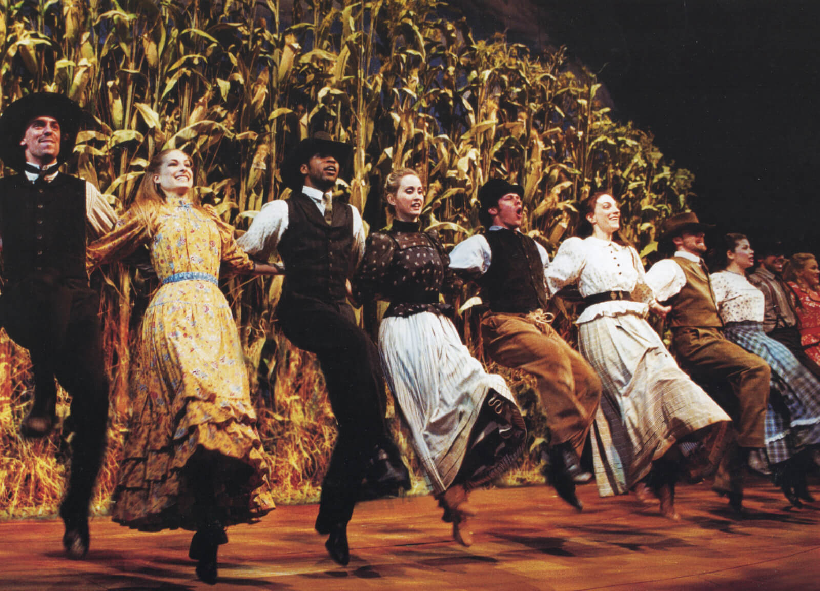 The Broadway cast of Oklahoma dance in front of a cornfield.