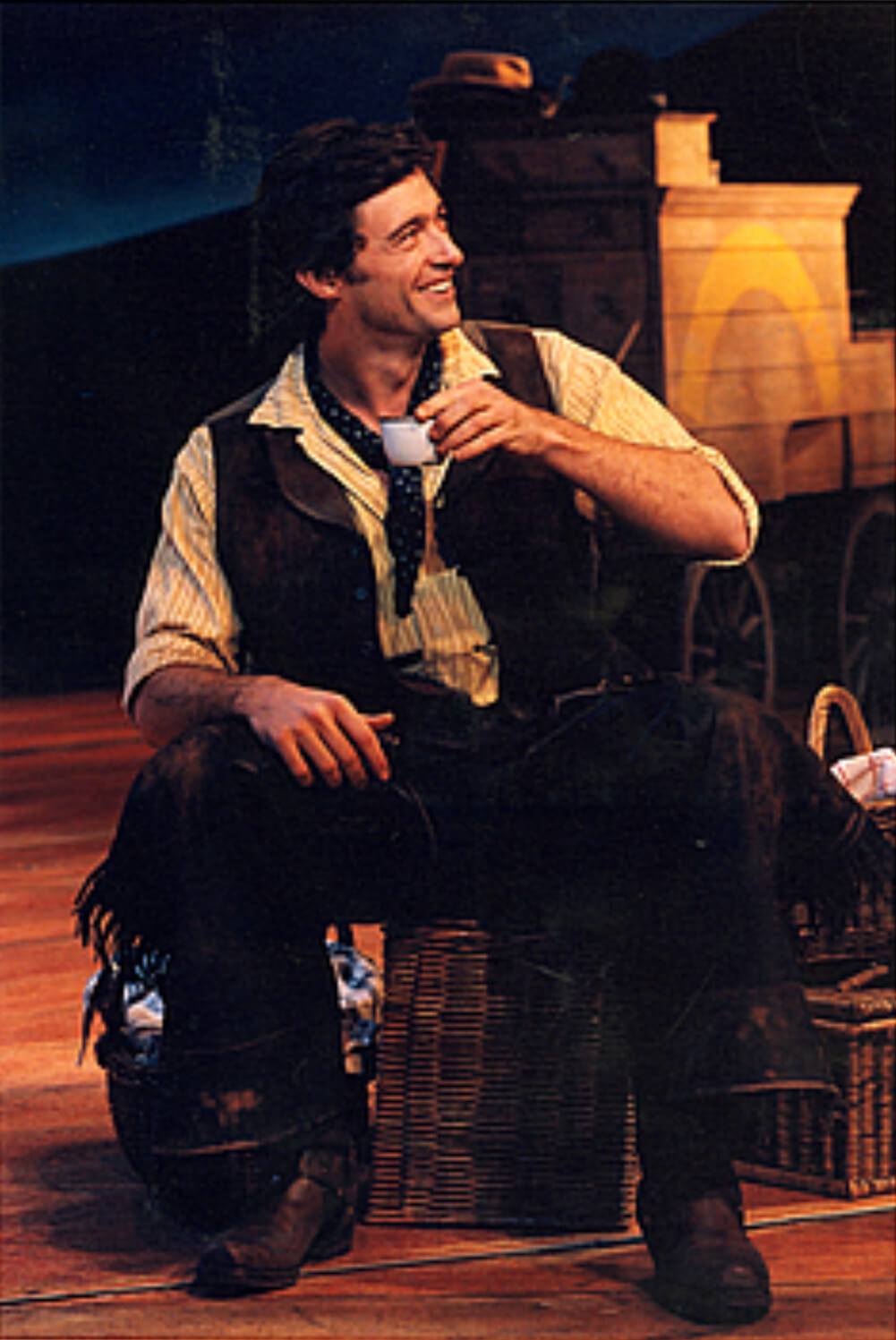 Curly (Hugh Jackman) holding his small cup of coffee while sitting and gazing at somebody on his left.
