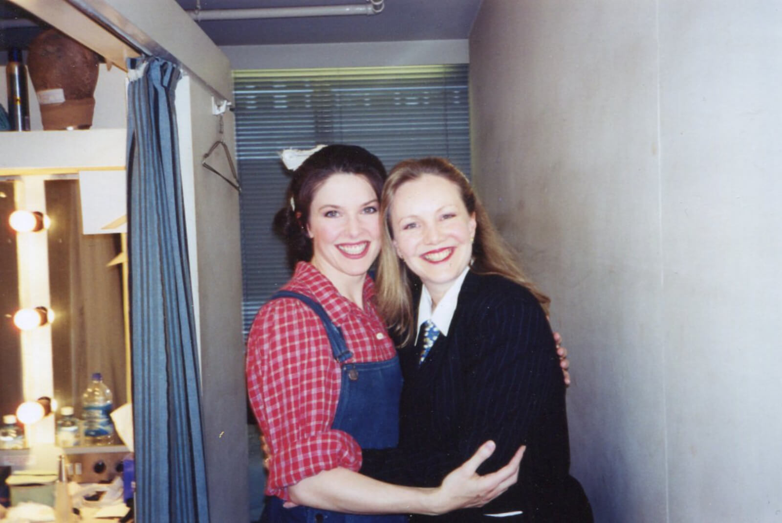 Susan Stroman in her all-black outfit with white collar, and Laurey Williams (Josefina Gabrielle) in the dressing/powder room backstage, smiling for the camera.