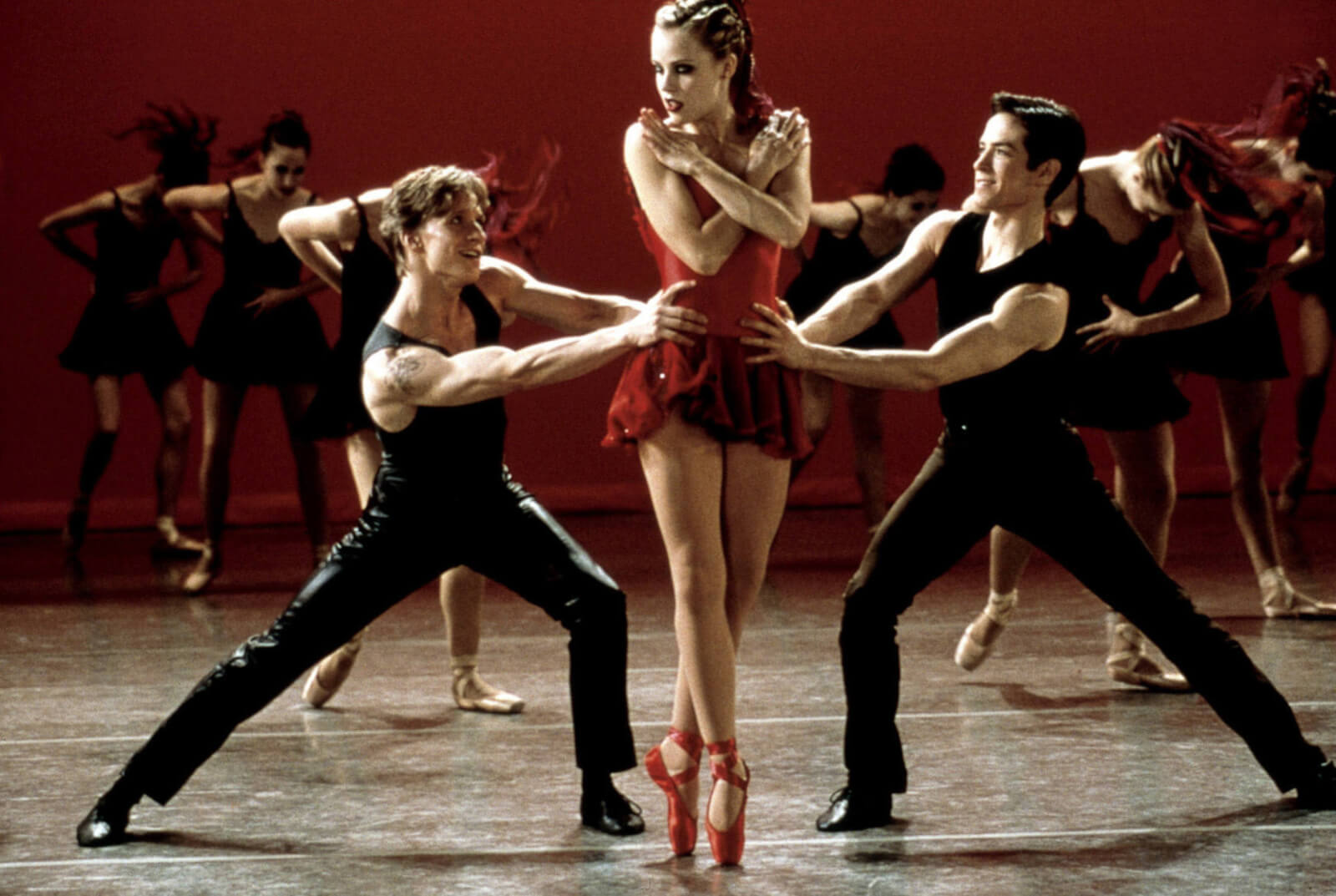 """Ethan Stiefel, Amanda Schull and Sascha Radetsky performing the finale in """"Canned Heat"""" from Center Stage. She is in a red costume with red pointe shoes. The men have their hands on her waist vying for her attention."""