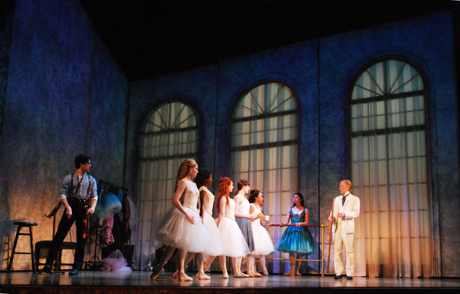 The ballet class from the musical Little Dancer. Ballet dancers dressed in white are listening to their ballet master. A young violinist looks on.