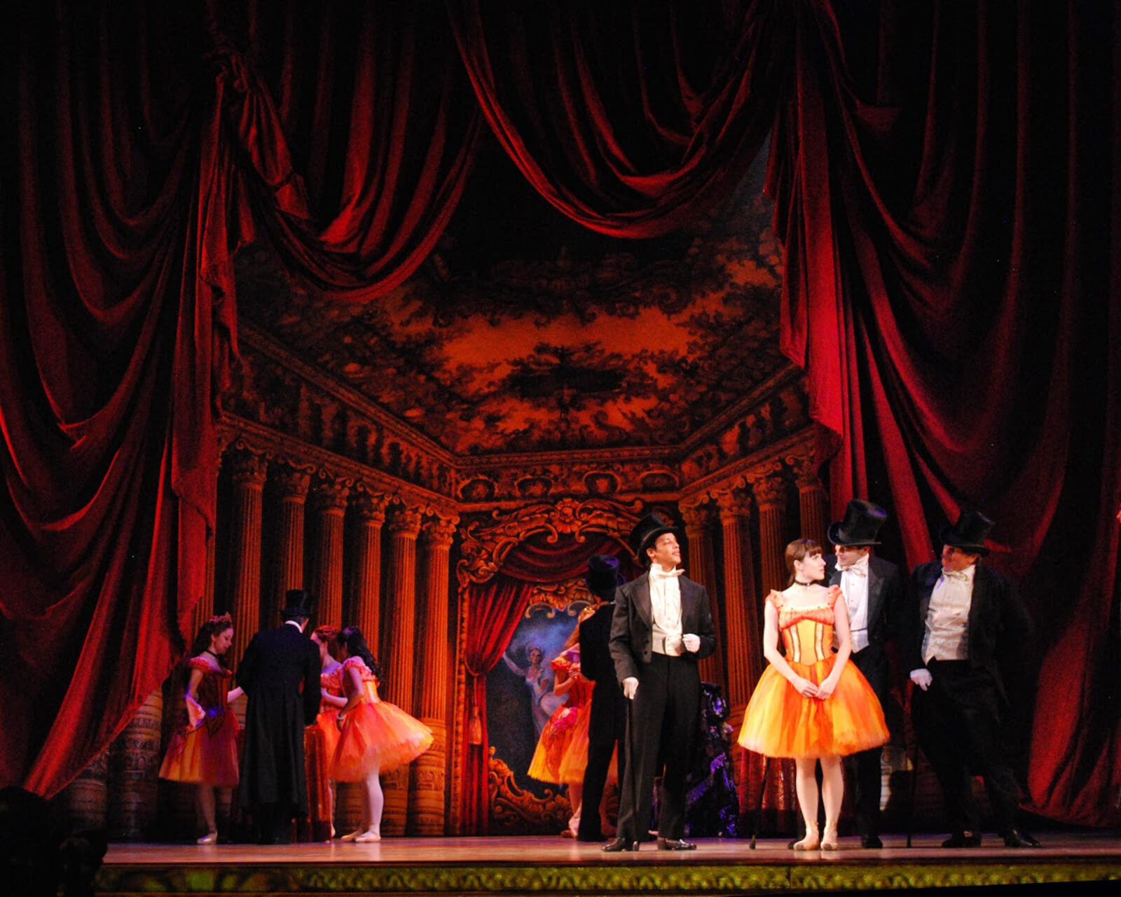 Marie (Tiler Peck) surrounded by the abonnés in the Foyer de la Danse. She is dressed in her butterfly tutu, the men are in their top and tails. There is red lighting on the set.