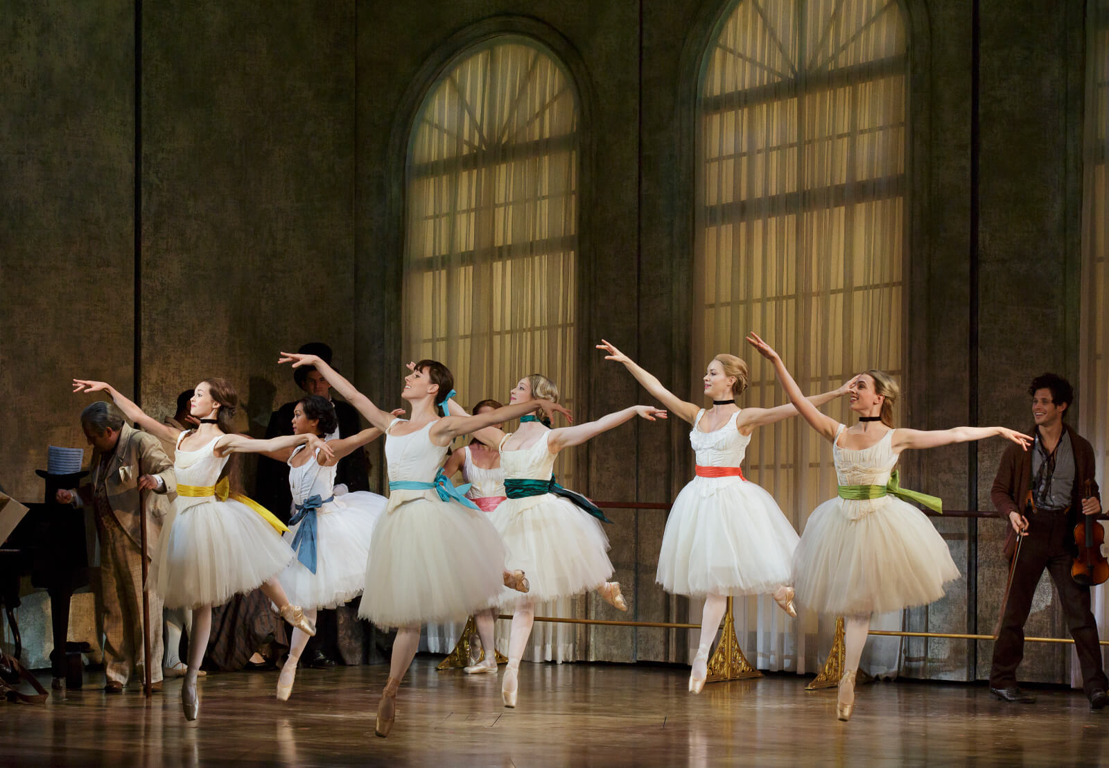 Marie and other ballerinas wearing white ballet outfits with matching colorful hair and belt bows, practicing in a ballet studio with huge windows. A man holding his violin is looking very happy at the back.