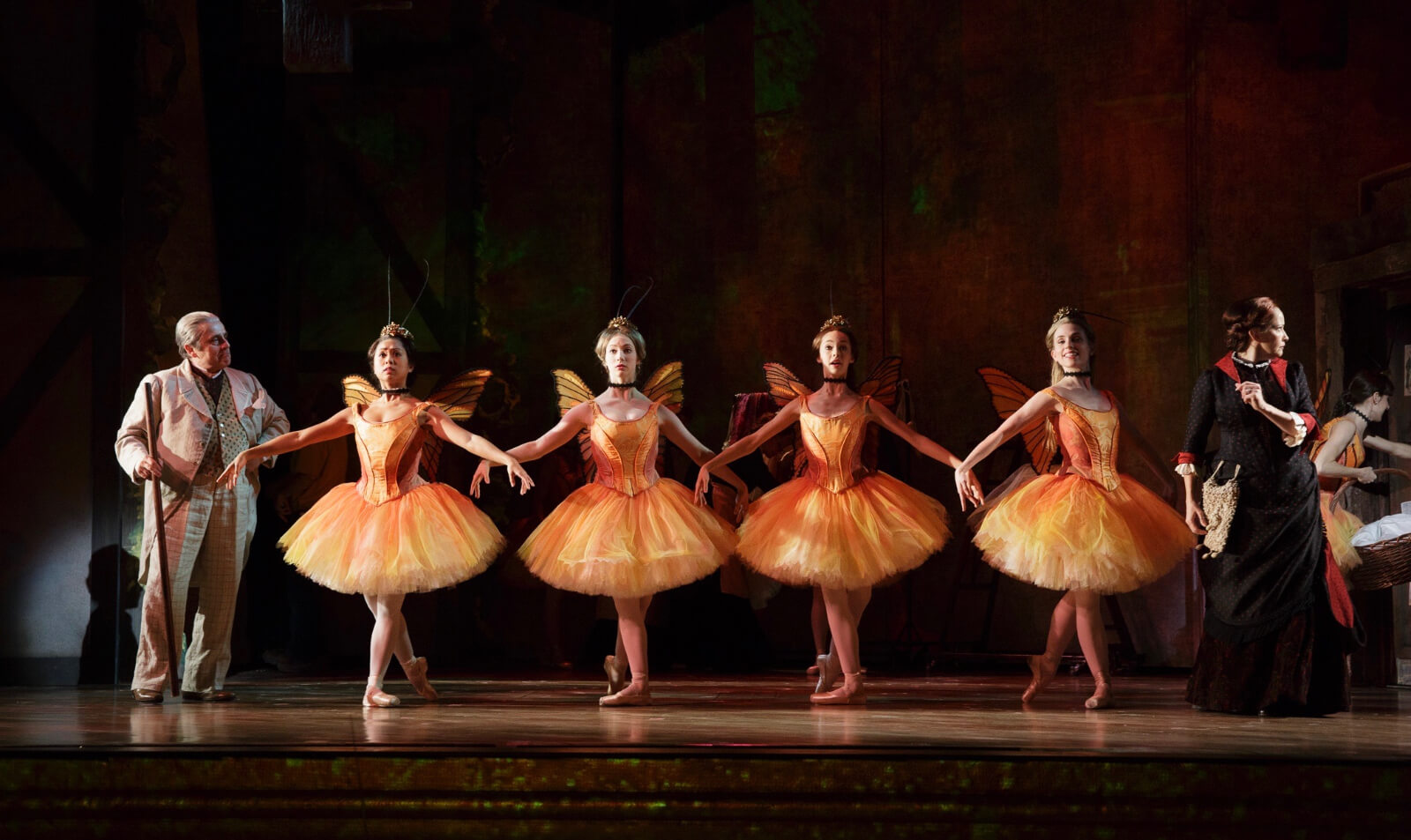 Four ballerinas in orange ballet outfits with matching wings and antenna, with arms in second position and feet in fourth position, being observed by their teacher.