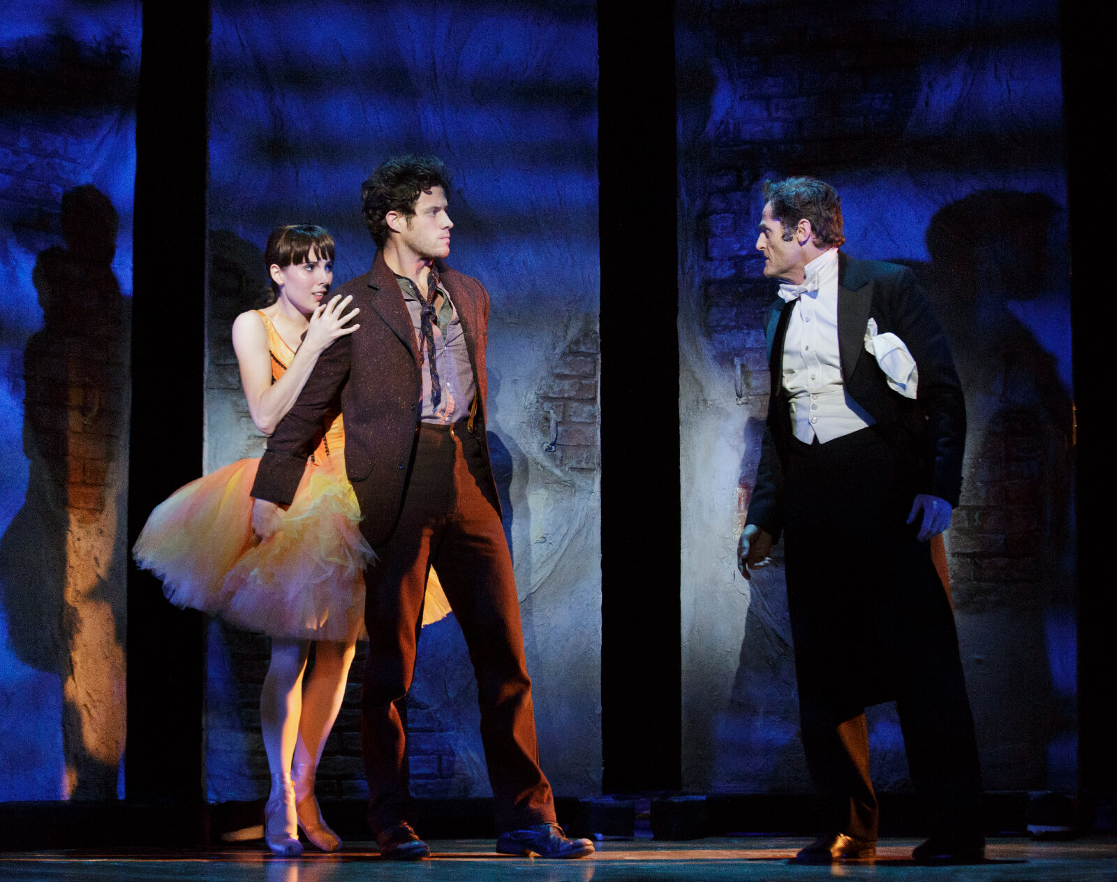 Marie (Tiler Peck) being protected by Christian (Kyle Harris) as Philippe (Seán Martin Hingston) threatens them in the musical Little Dancer.