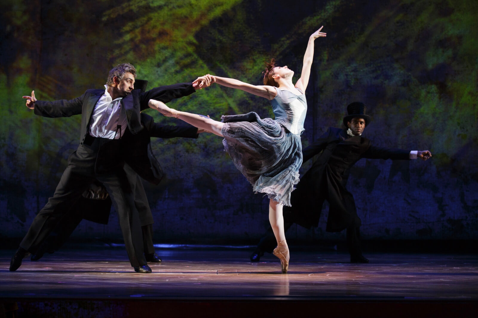 Marie in a powder blue ballet dress and beige shoes, doing a show-stopping arabesque with a partner in a suit.