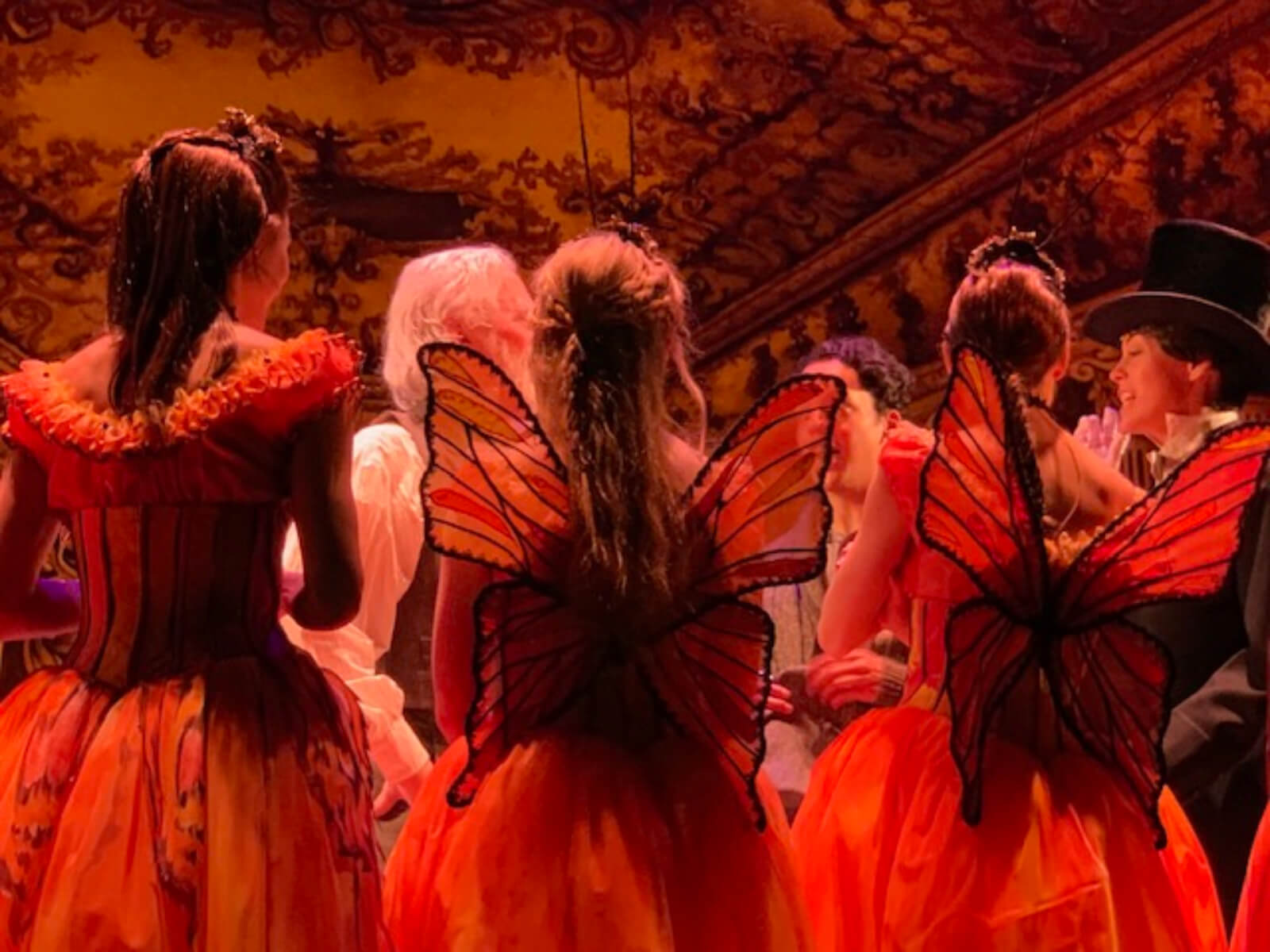 Ballerinas in butterfly costumes, with matching antennas and wings, being instructed before the show. They are in a huge hall with fancy painted walls and ceilings.