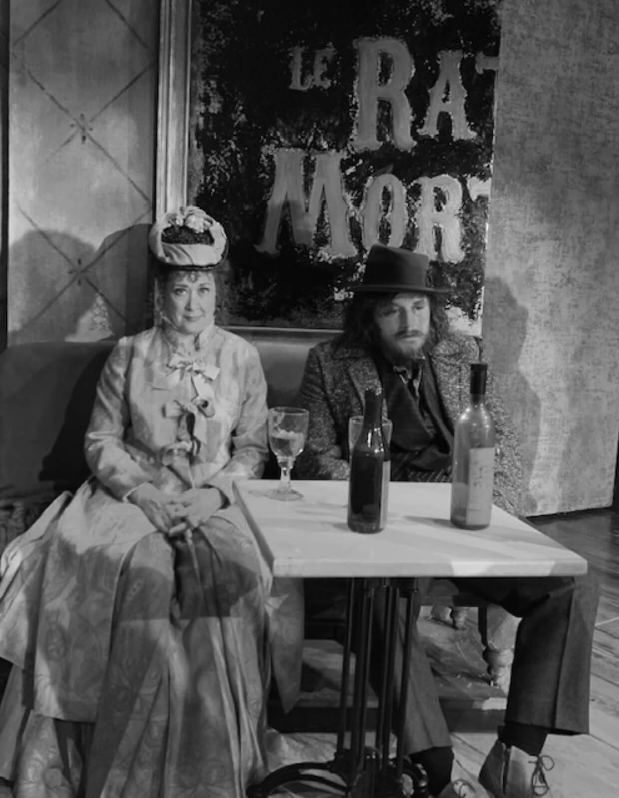 A black and white photo of Karen Ziemba and Jimmy Borstelmann in a bar. Karen is wearing a hat and a big dress, while Jimmy in a hat and a suit, is slouching and looks drunk. They are L'Absinthe drinkers.