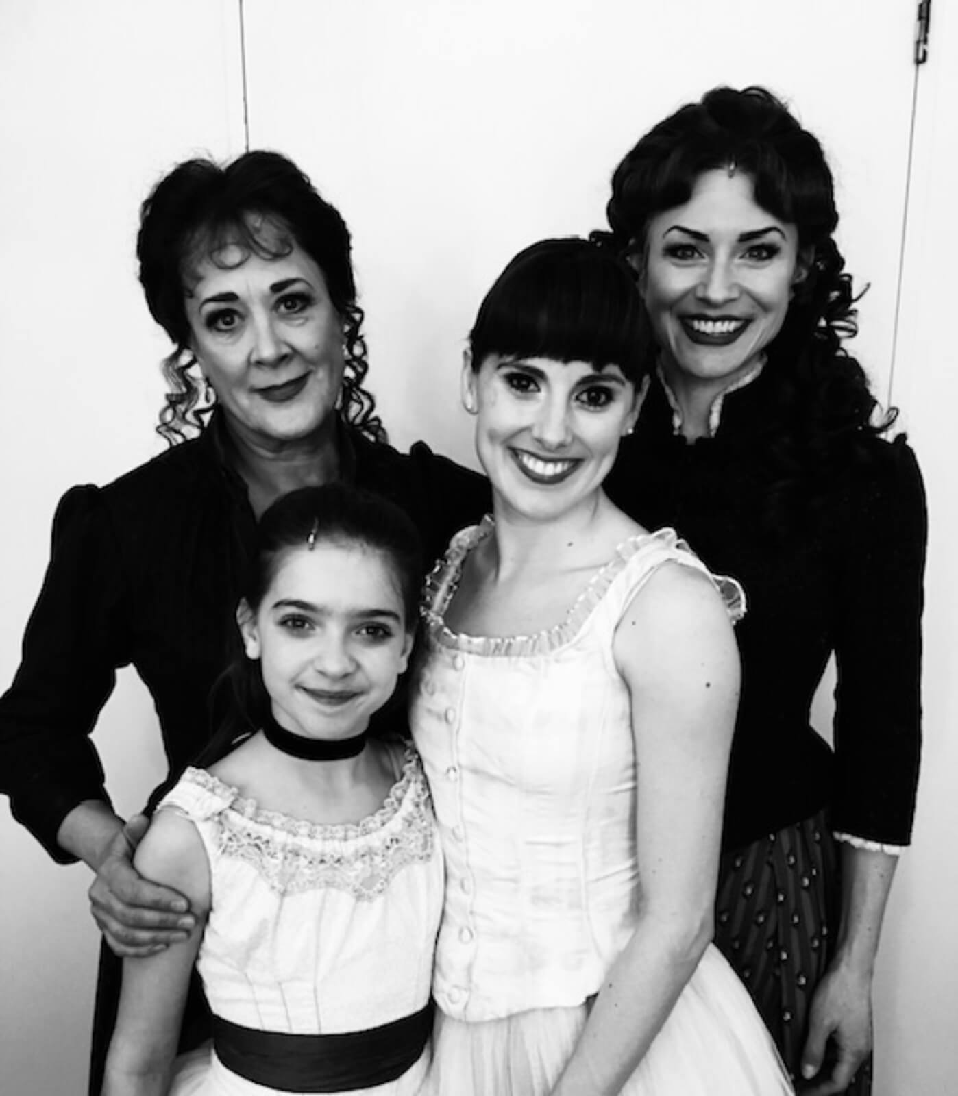 A black and white photo of Marie (in her character's costume) and her family, in formal wear.