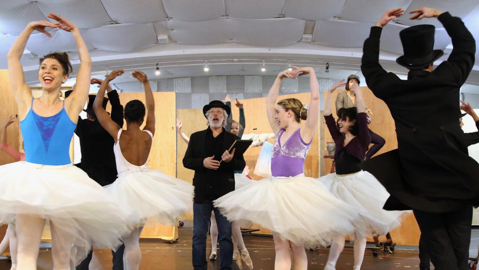 The cast in their beautiful and colorful leotard tops and white tutus, with male dancers in a black hat and a suit, during rehearsals, having fun while being serious with training at the same time. Degas stands in the middle.