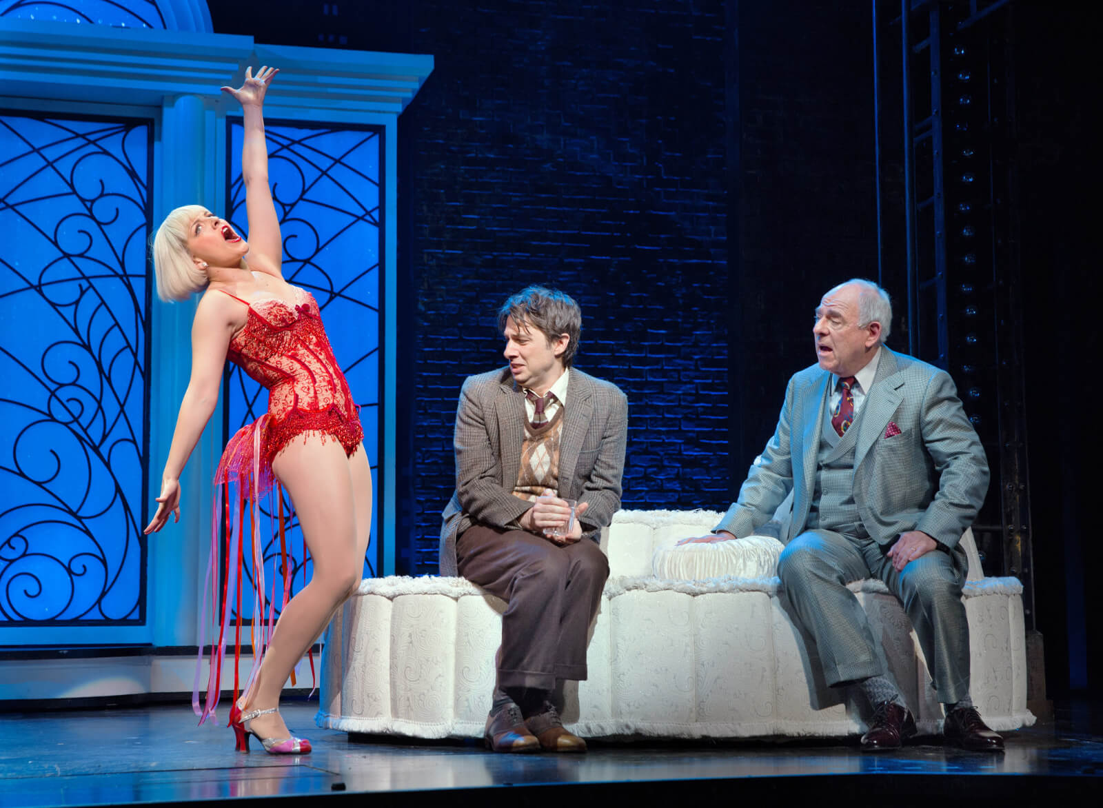 Olive Neal (Heléne Yorke) is dressed in a red sparkly leotard and singing about a hot dog. Zach Braff and Lenny Wolpe look on uncomfortably.