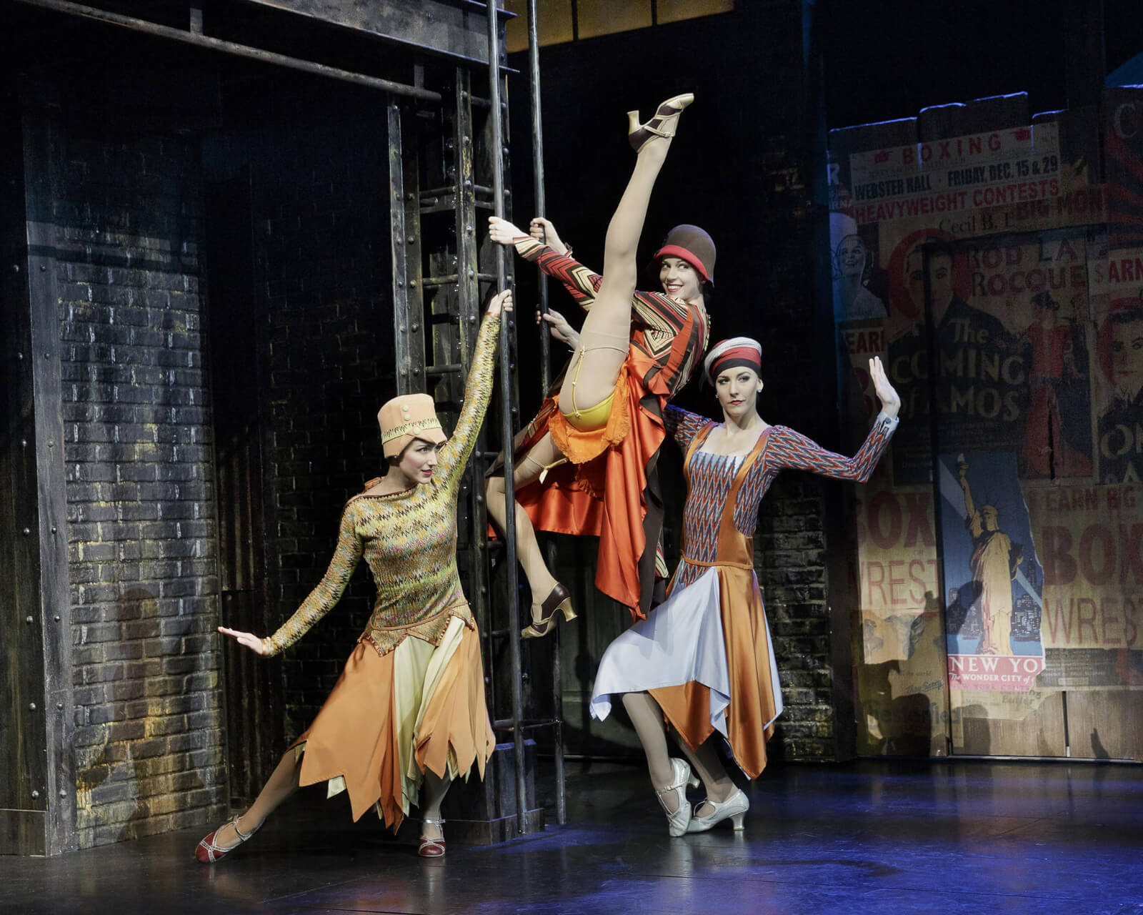 3 women in period flapper costumes dancing on a ladder. One has climbed the ladder and is in an extended battement.